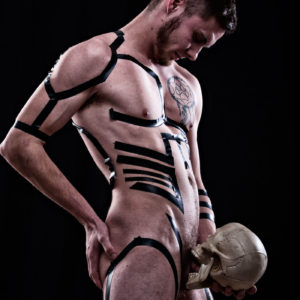 Male model holding skull to crotch